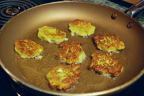 some roughly formed patties, frying in olive oil